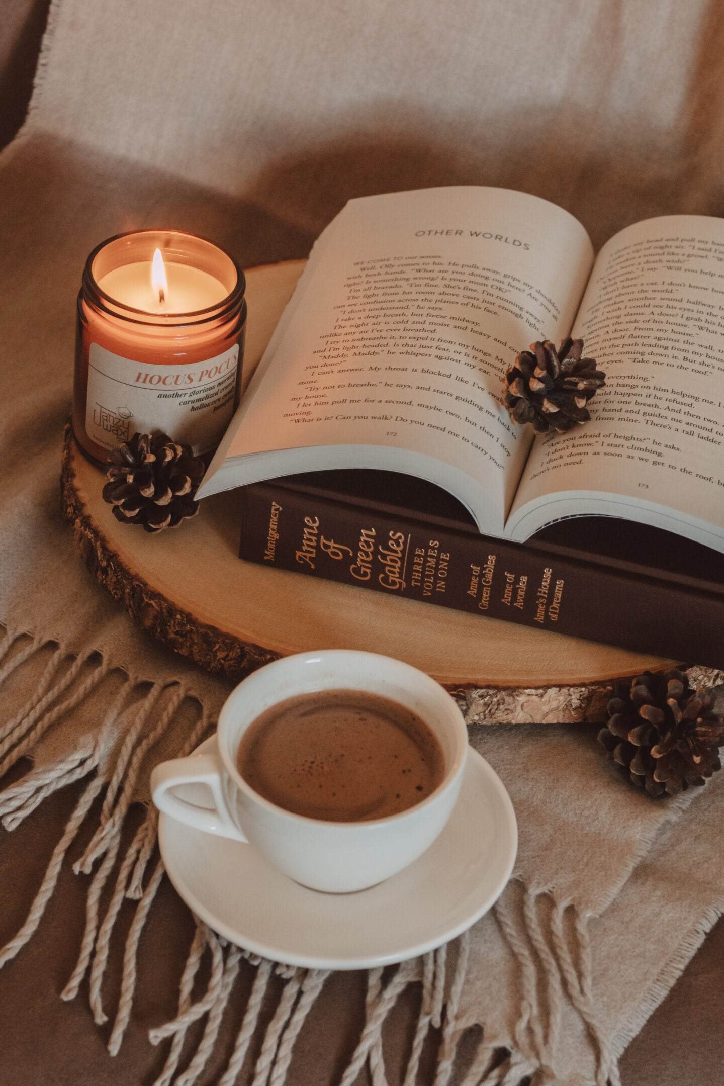 mug of swirling mocha sitting next to two books on top of a wooden board next to a lit candle