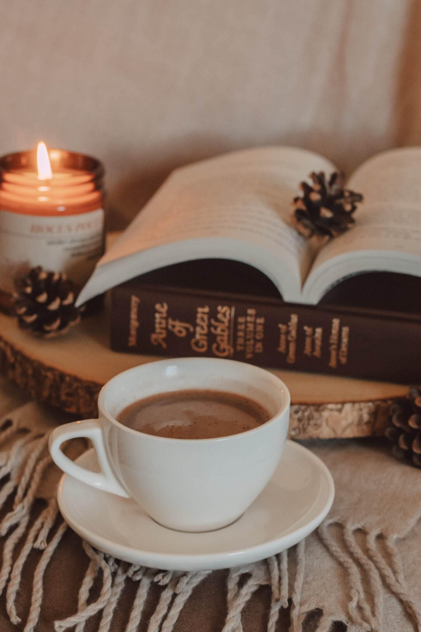 mug of mocha in front of vintage copy of anne of green gables book with a burning candle and pinecones