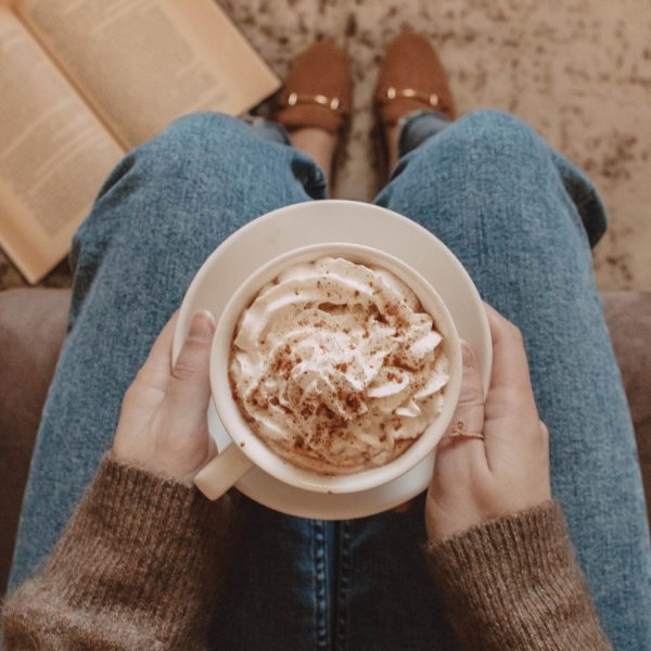 hands holding a mug filled with whipped cream and cinnamon on top of lap with book laying on the floor