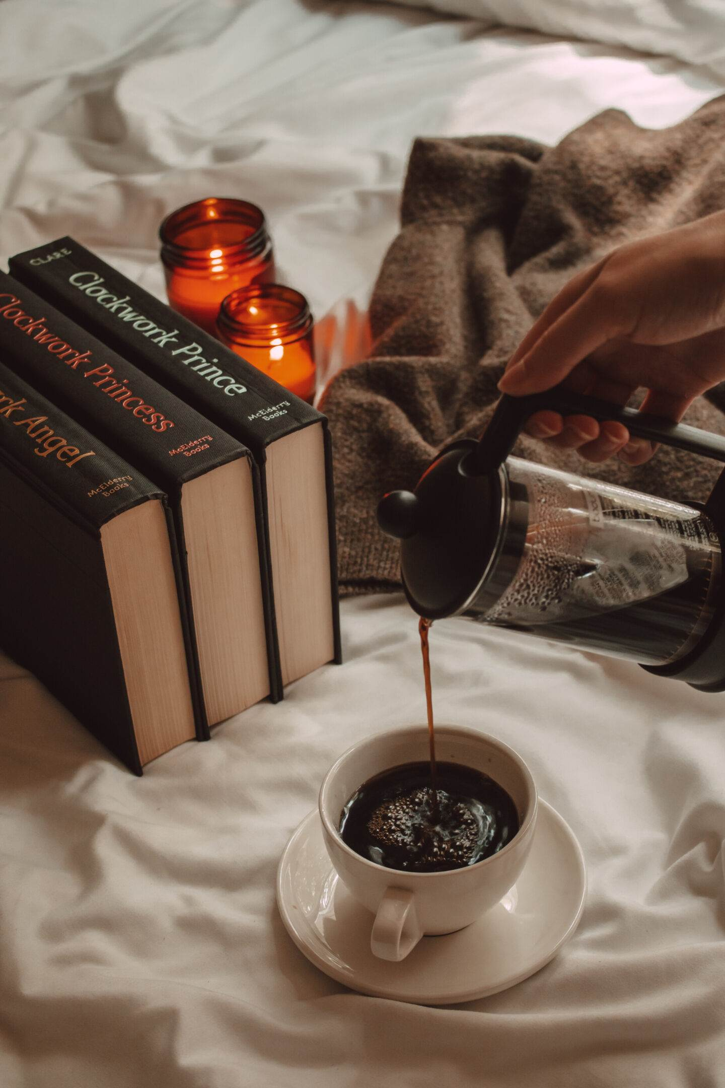 pouring black coffee from a french press into a mug with The Infernal Devices trilogy of books nearby and two lit candles
