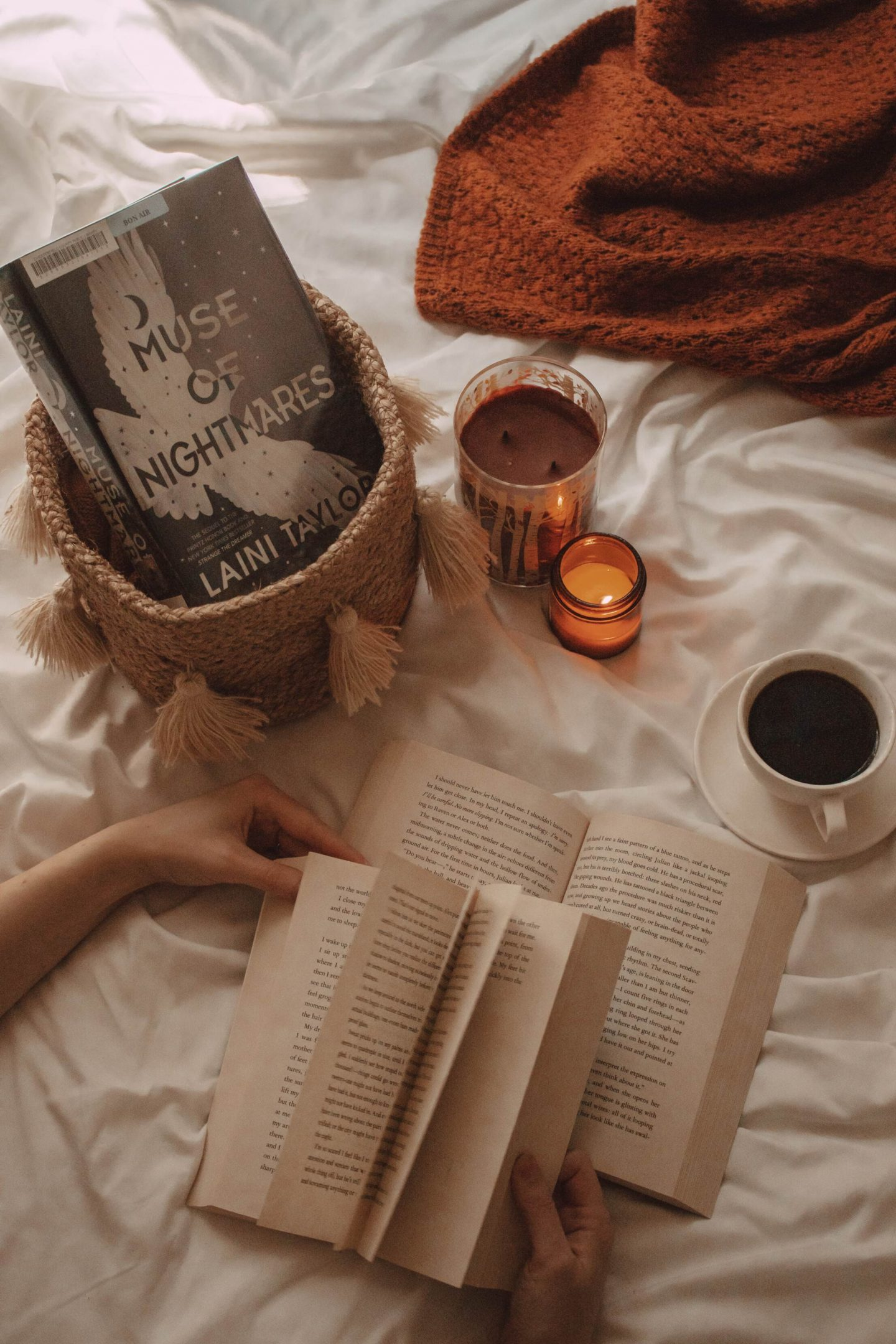hands flipping pages of a book while it's laying on top of another book. muse of nightmares novel sits in a basket next to a lit candle and a mug of coffee.