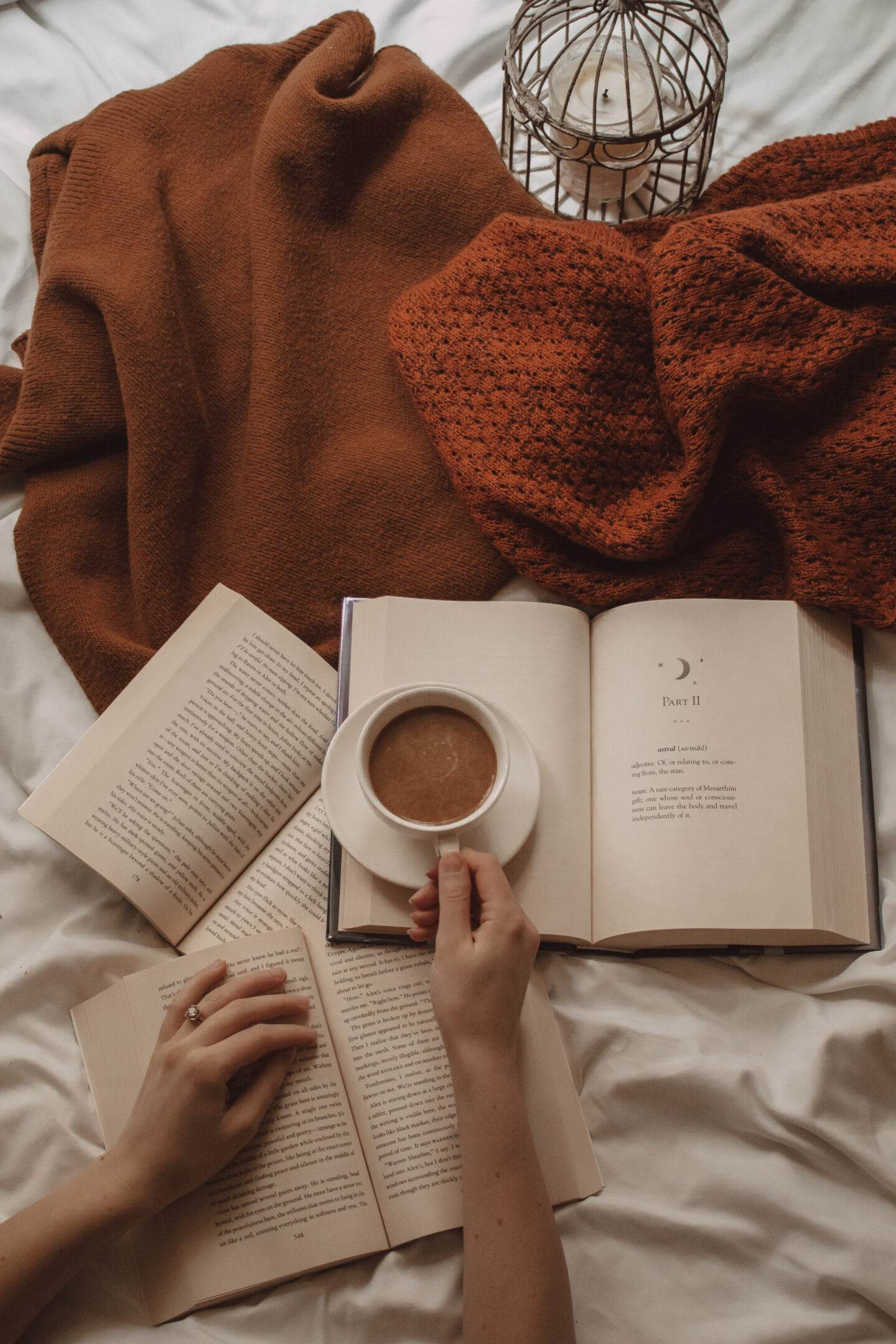 hand holding mug of coffee on top of an open book with other open books lying beneath and orange sweaters above