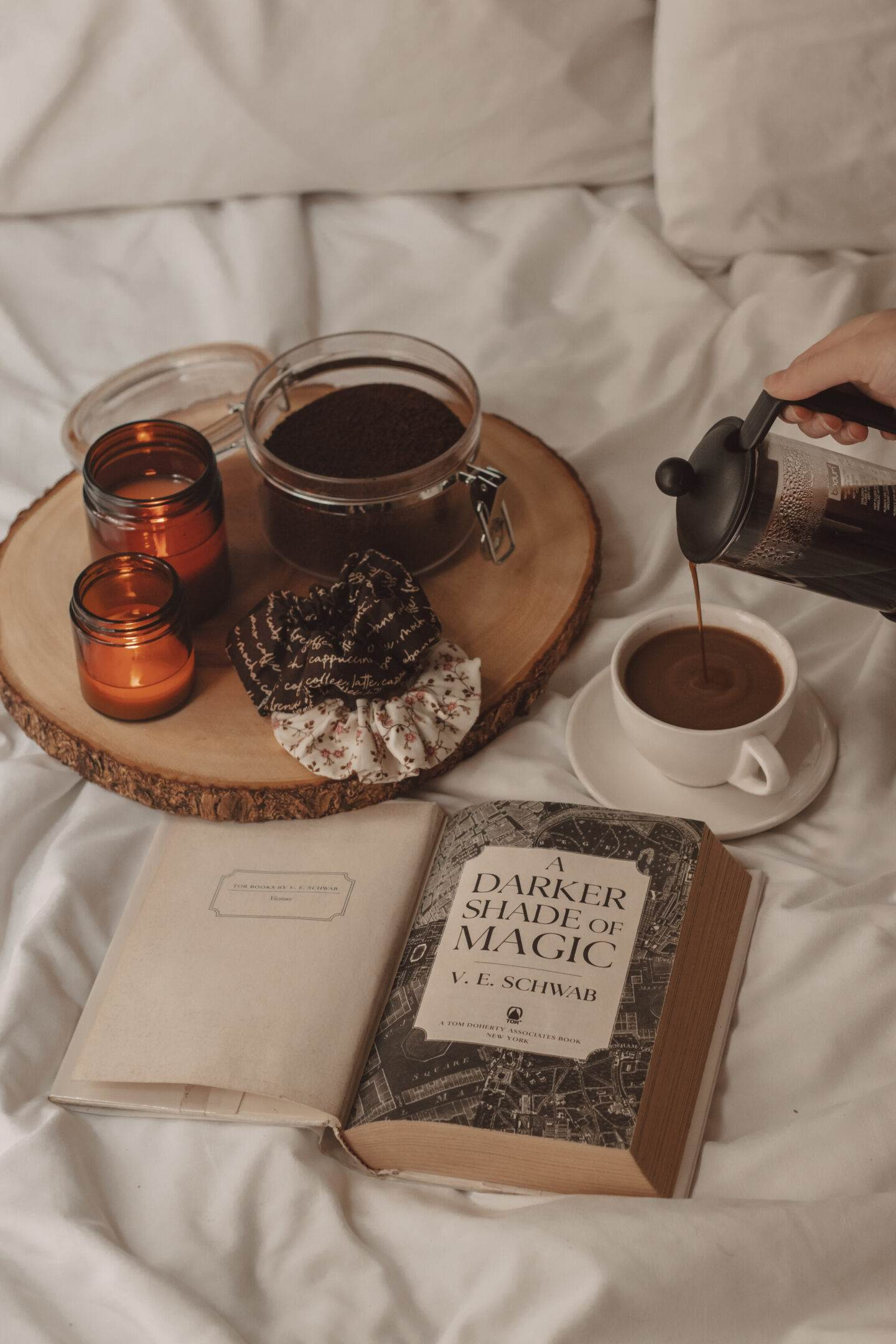 a darker shade of magic cover page opened next to a hand pouring coffee into a mug. a container of coffee grinds lays open next to two lit candles and hair ties.