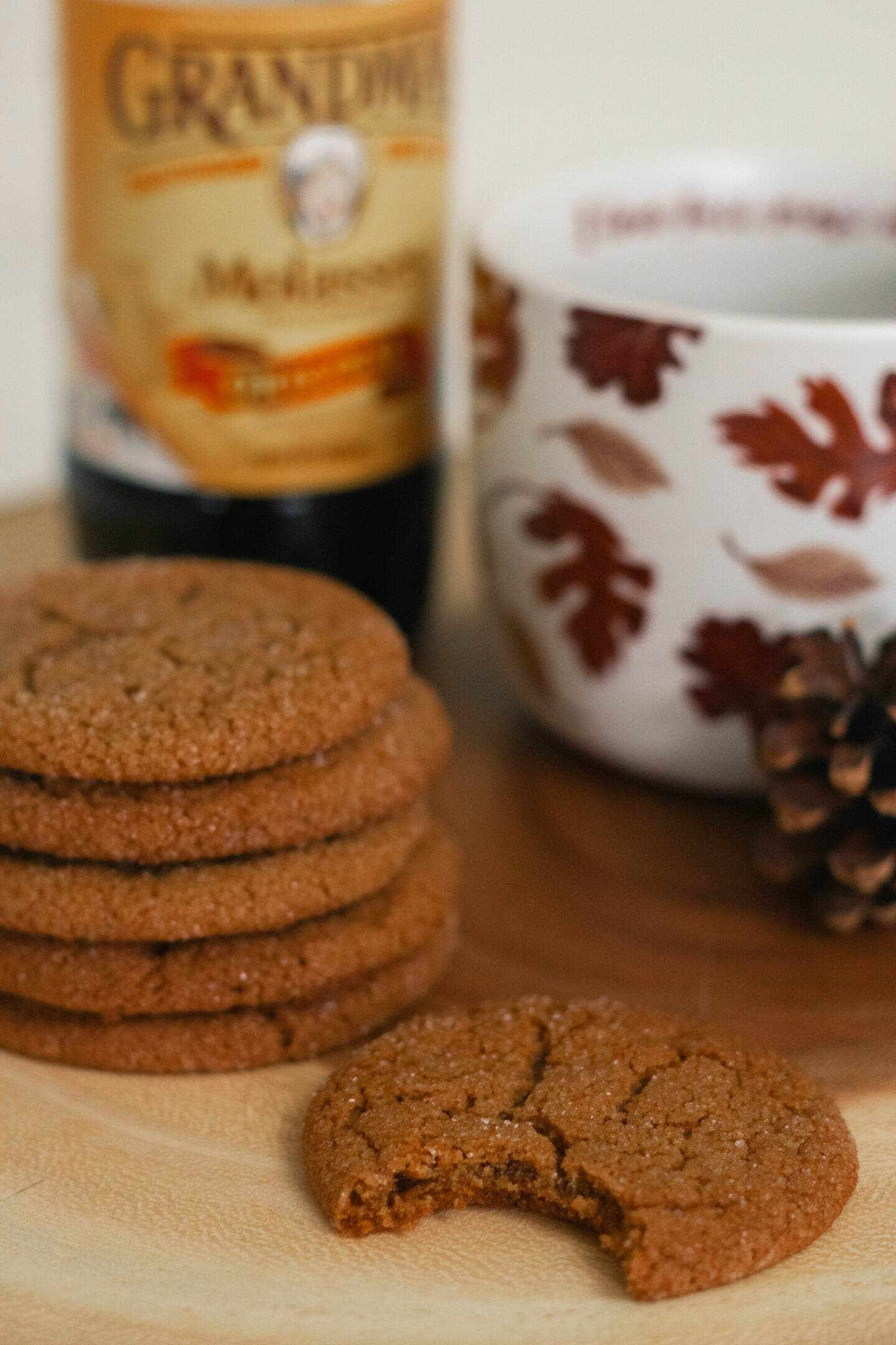 crinkle molasses cookies stacked on top of each other, next to a jar of molasses and a mug with leaves on it