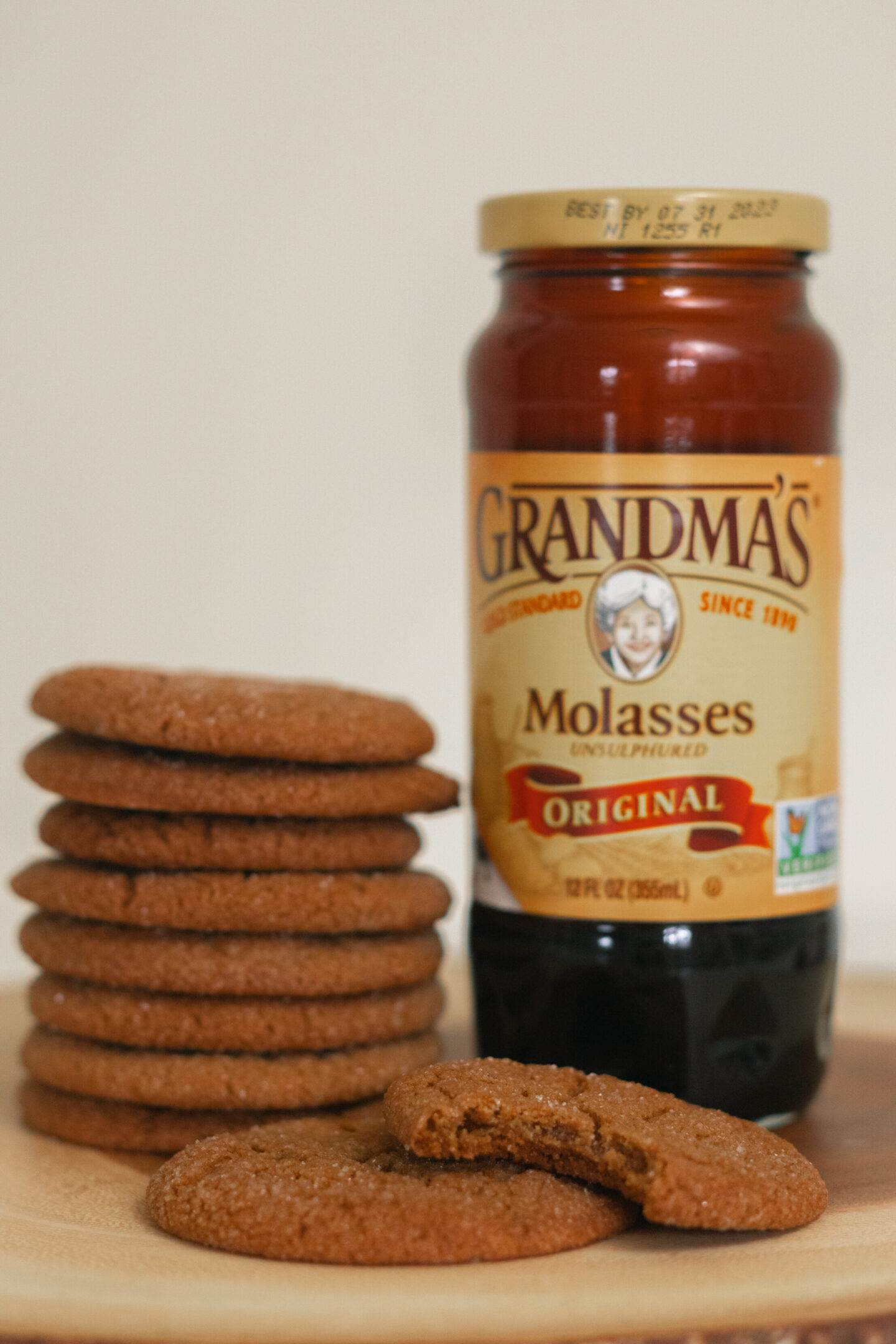 a jar of molasses placed next to a stack of cookies