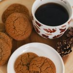 two cookies - one with a bite taken out of it - on a play next to a mug of black coffee