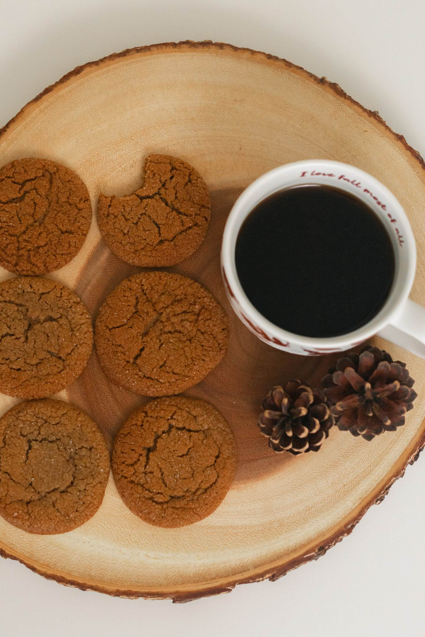 six crinkled molasses cookies next to a mug of black coffee
