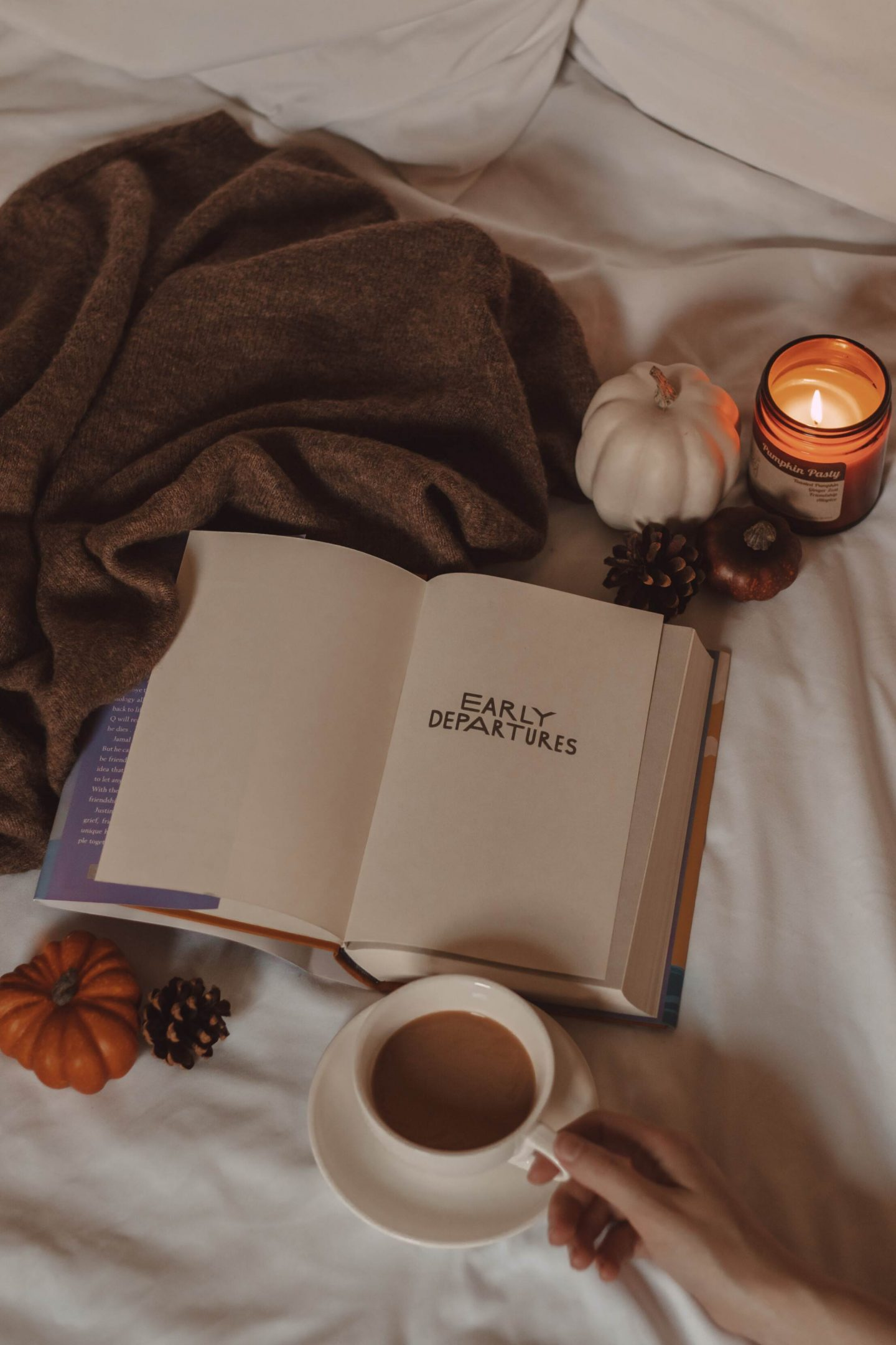early departures book lying open with a mug of coffee, a sweater, mini pumpkins, and a lit candle