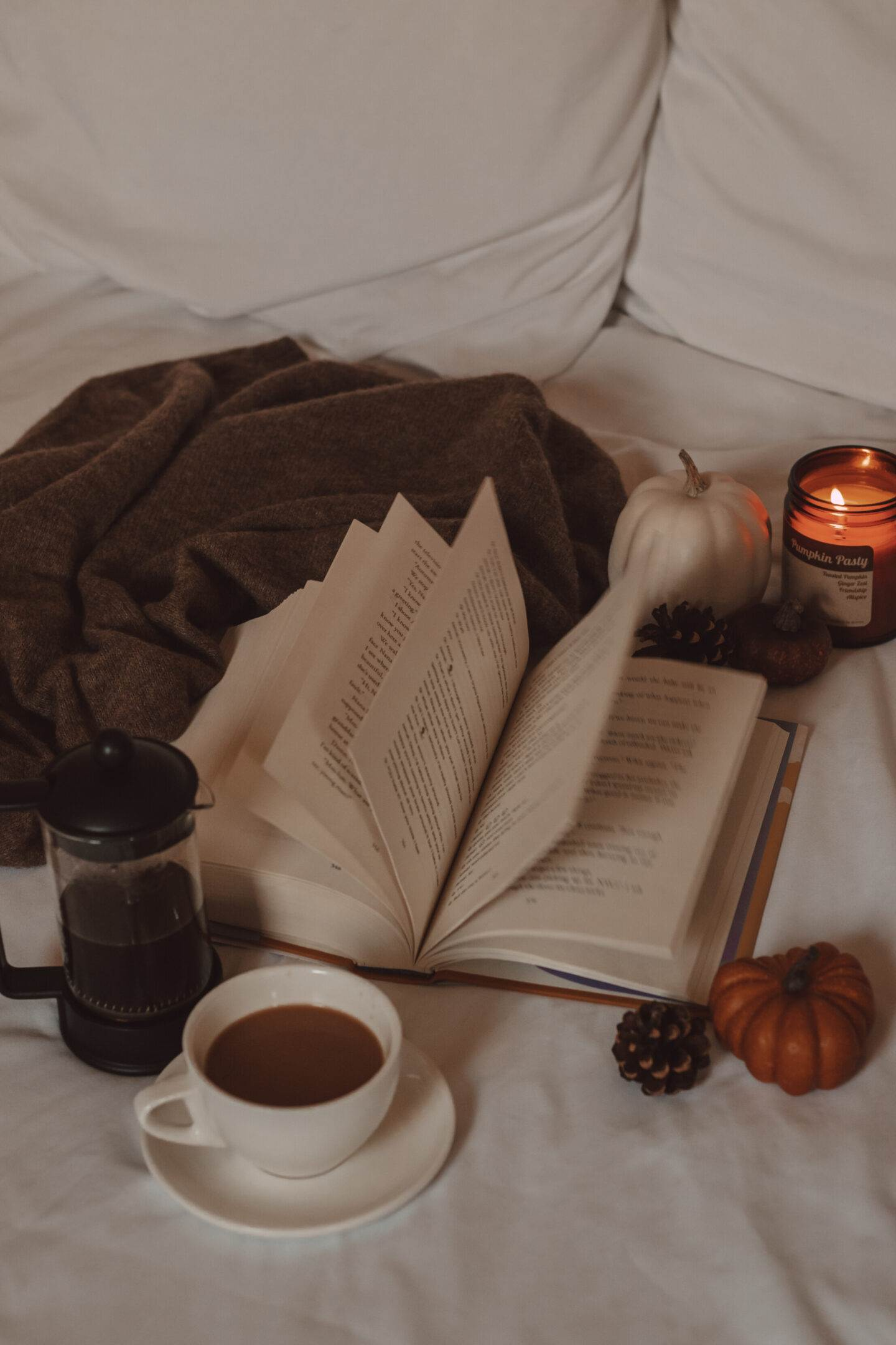 pages flipping in a book next to a french press and mug of coffee, mini pumpkins, and a candle