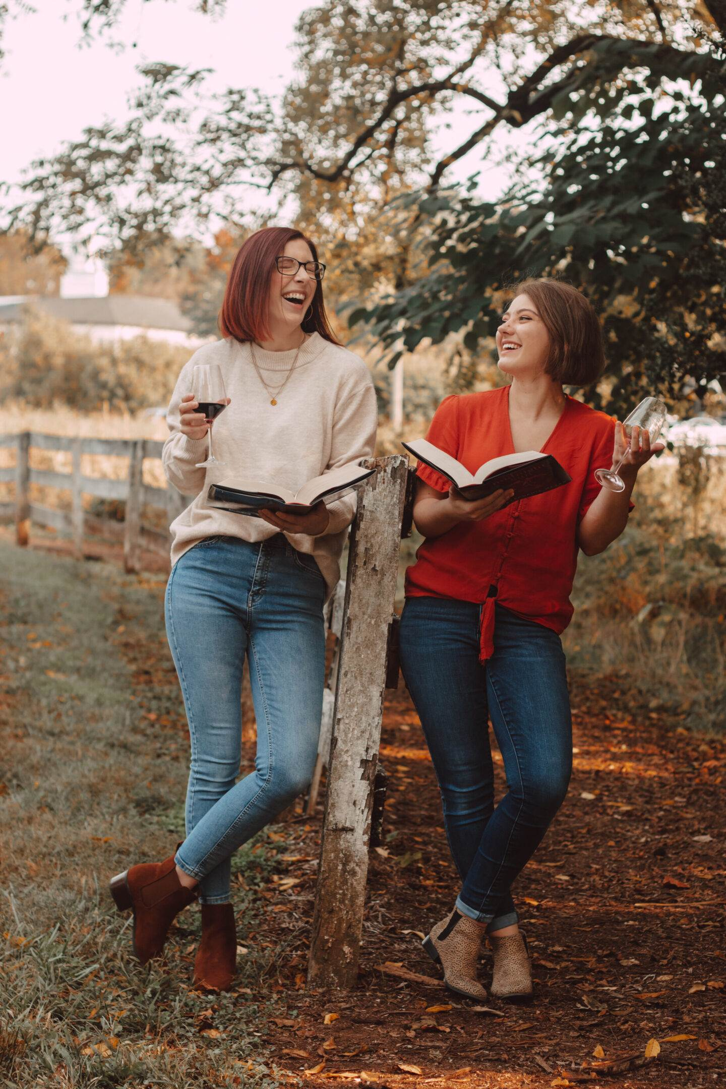two girls holding midnight sun and laughing by a fence