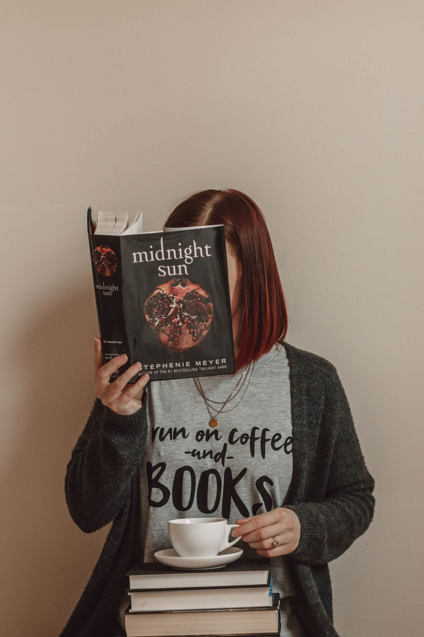 """girl holding midnight sun book in front of her face while wearing a shirt that says """"i run on coffee and books"""""""