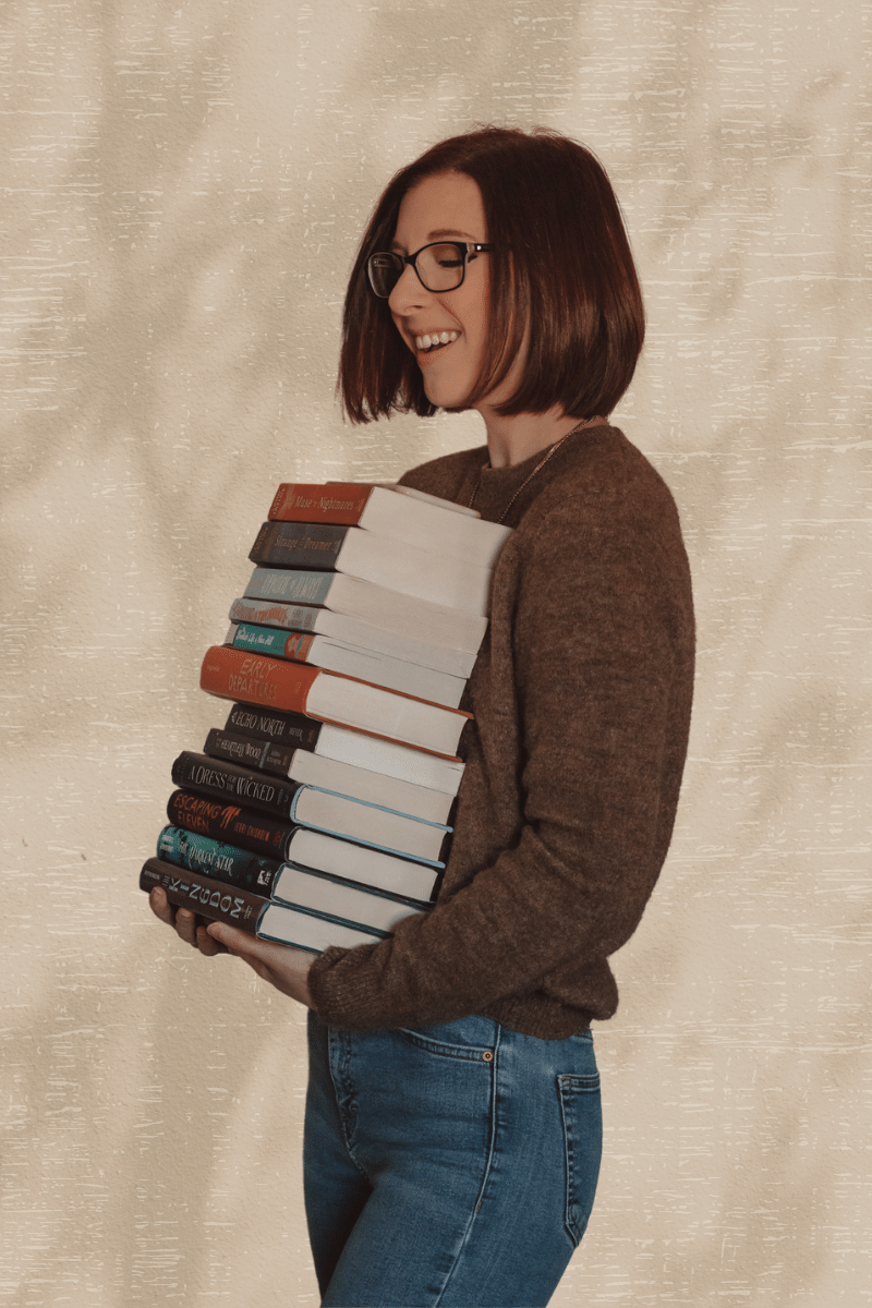 girl holding a large stack of books