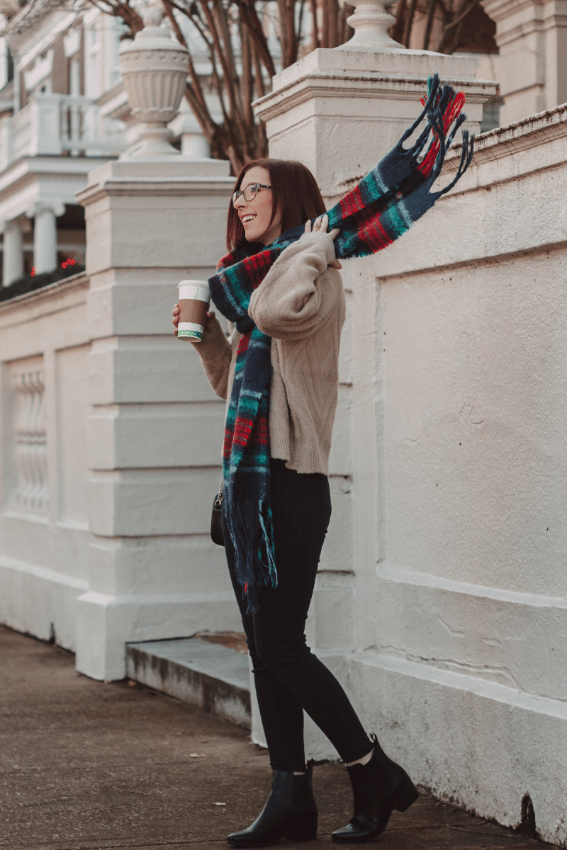 girl flips plaid wool scarf and holds coffee cup