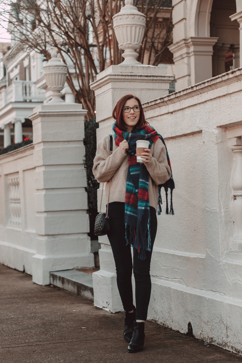 girl holding coffee wearing scarf in casual winter outfit