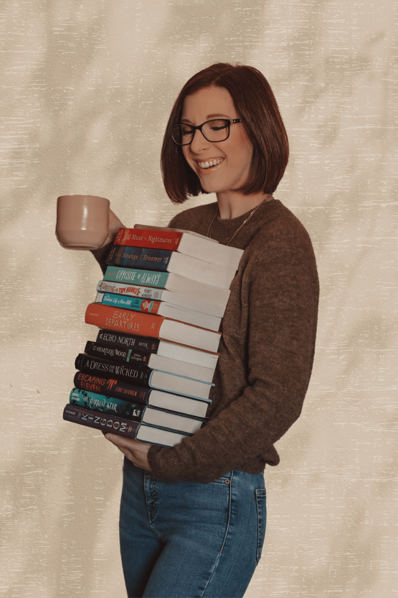 woman holding a stack of books and coffee mug