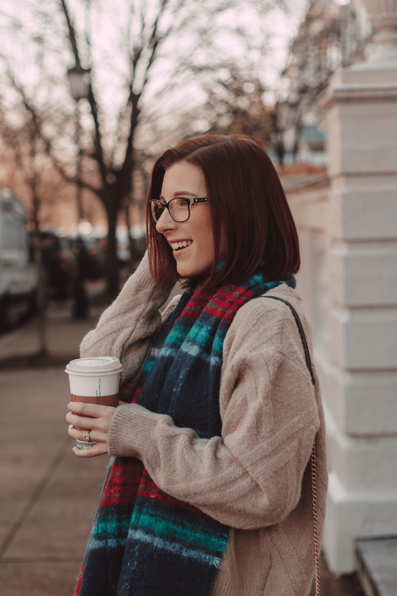 girl holding coffee with plaid scarf and taupe sweater