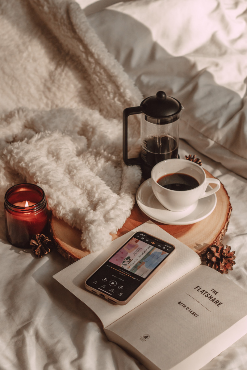 the flatshare audiobook and book with french press coffee and cozy blanket