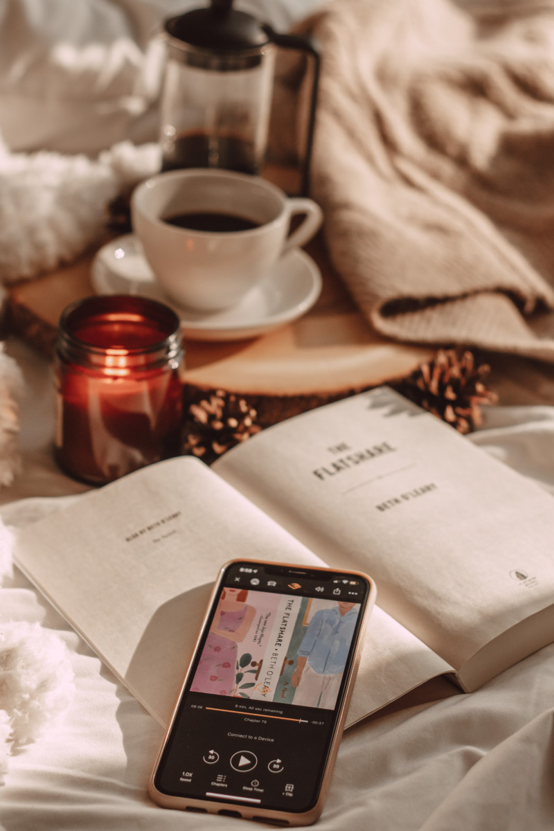 the flatshare audiobook on iphone with sunlight and candle and coffee