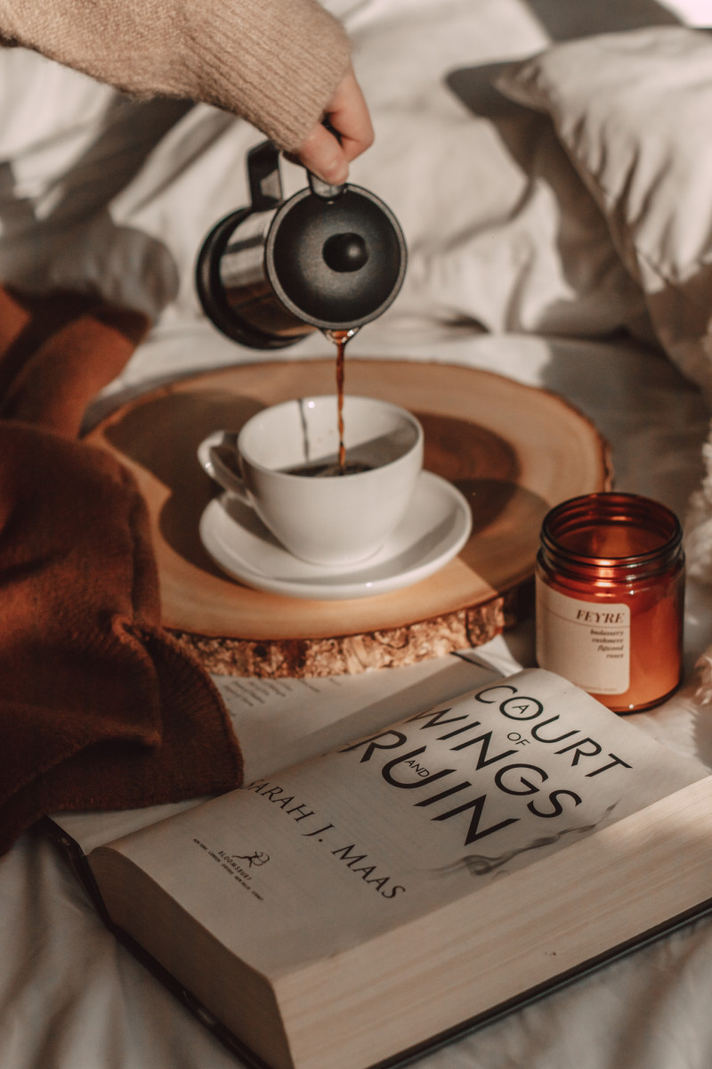 coffee pouring from french press next to a court of wings and ruin book and feyre candle