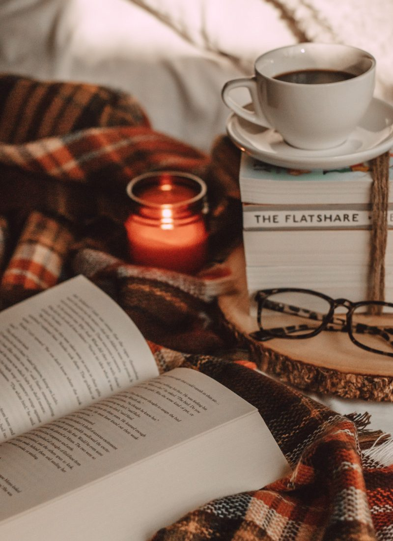 open book with candle and book stack with coffee and glasses