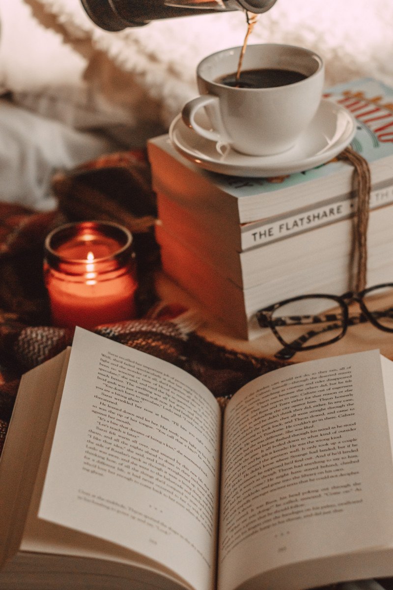 open book with pages flipping and burning candle and a mug of coffee on book stack