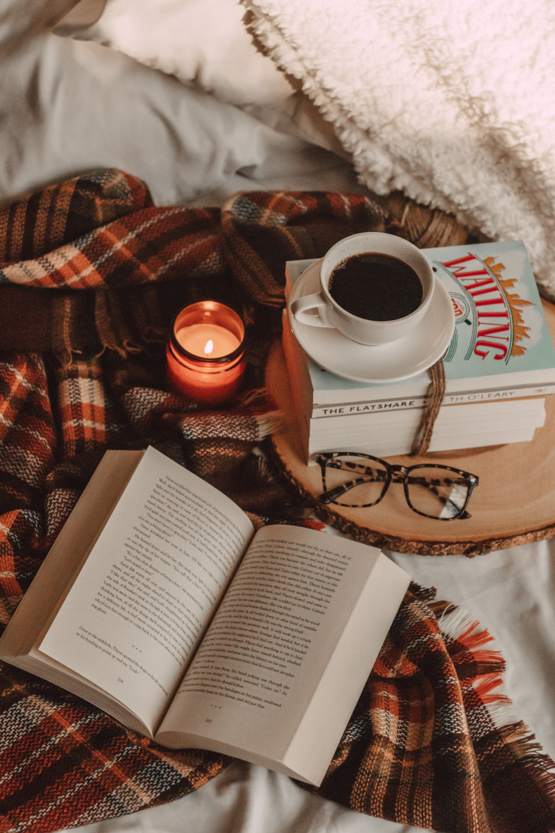 open book on plaid blanket with mug of coffee and candle