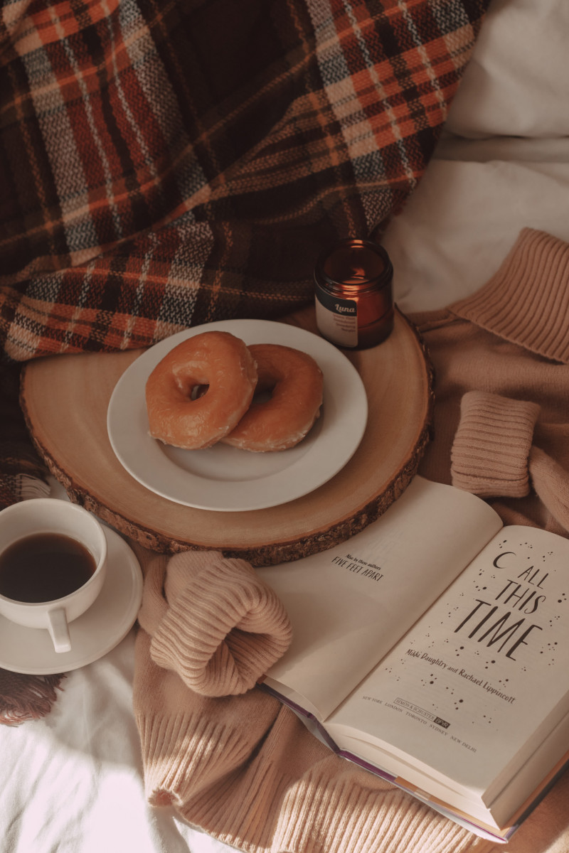 donuts and a mug of black coffee next to all this time book with a plaid scarf and camel colored sweater