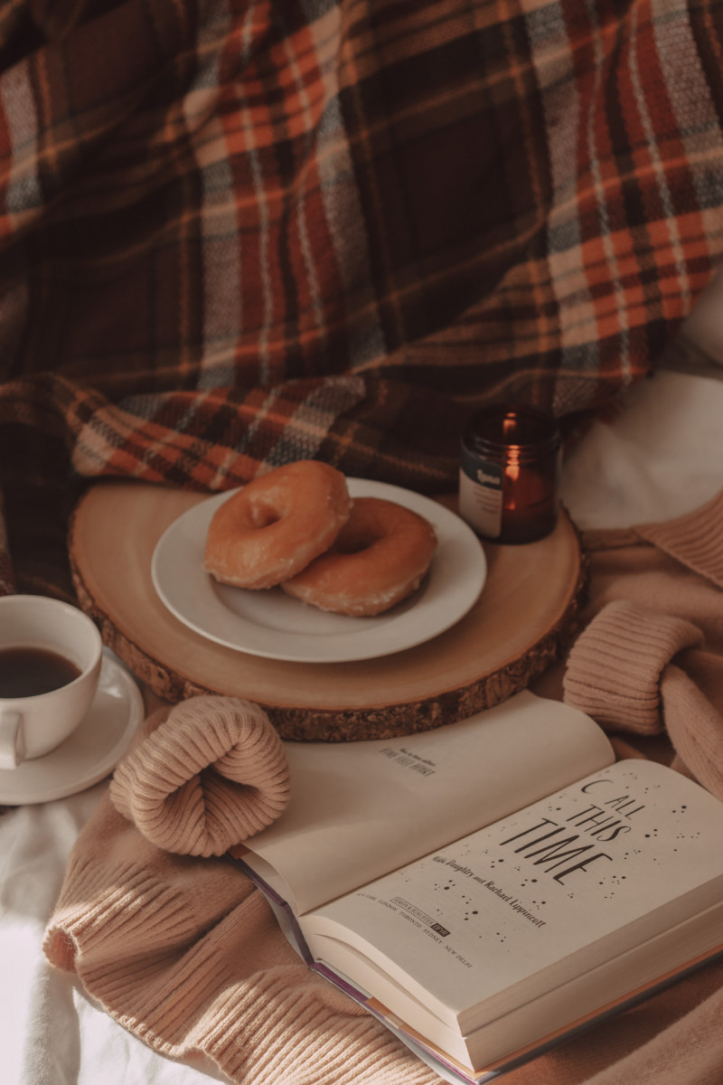 all this time book open on top of a tan turtleneck sweater with donuts and coffee