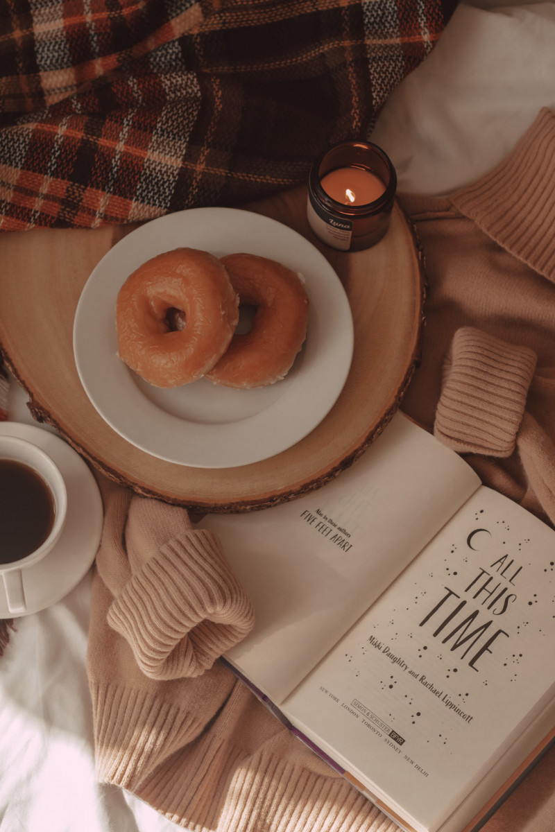 coffee mug and donuts laid on top of a taupe sweater with all this time book open to title page