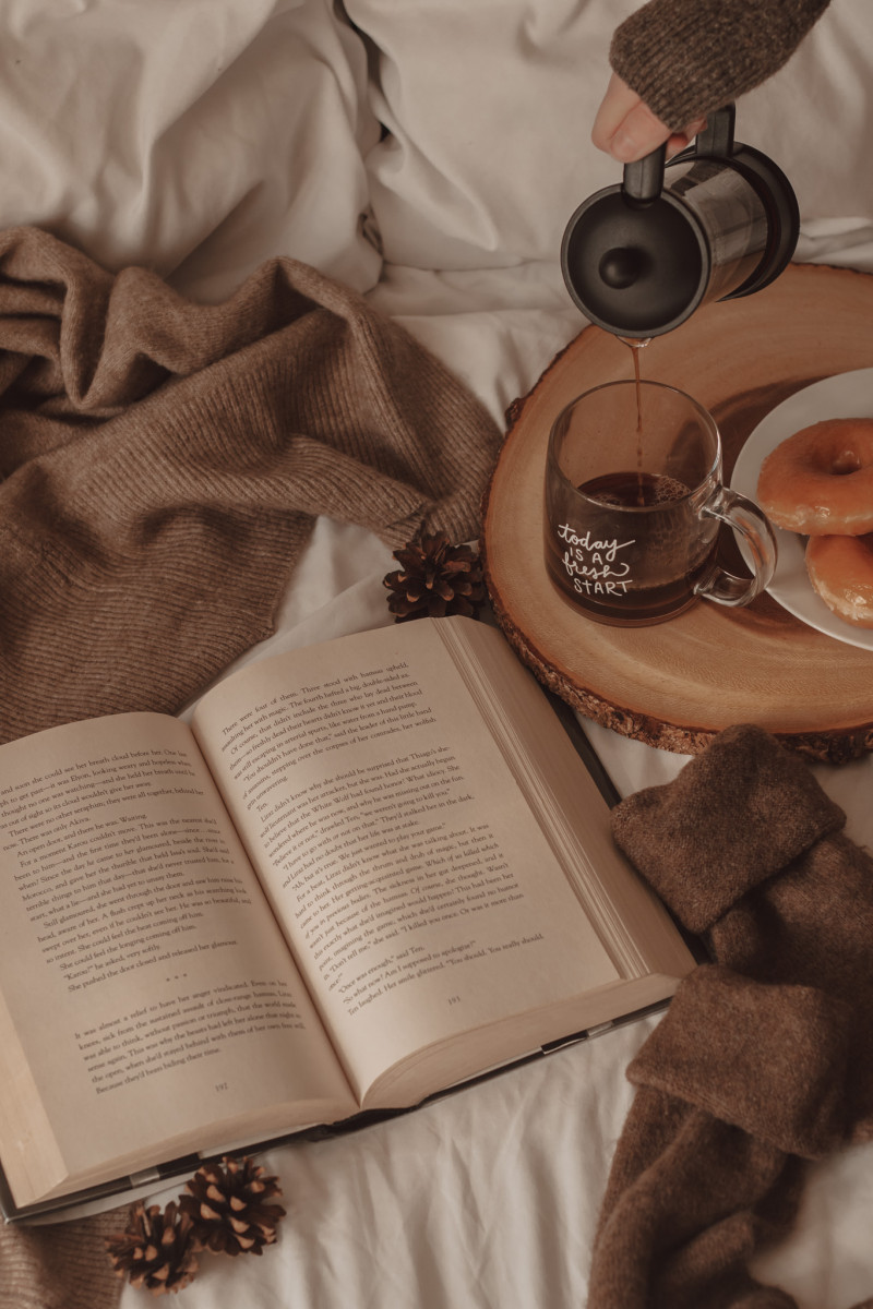 coffee being poured into a clear mug with a book and donuts