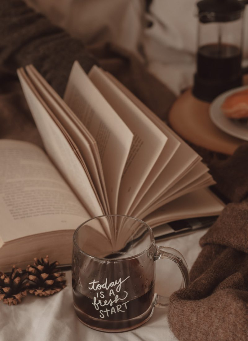 """today is a fresh start"" clear coffee mug in front of a book with the pages being flipped"