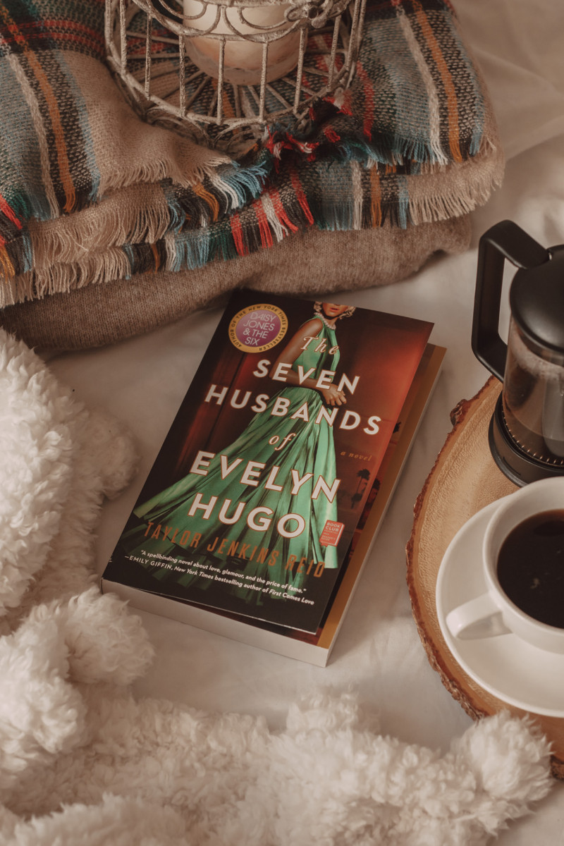 the seven husbands of evelyn hugo book next to multiple blankets and a mug of black coffee