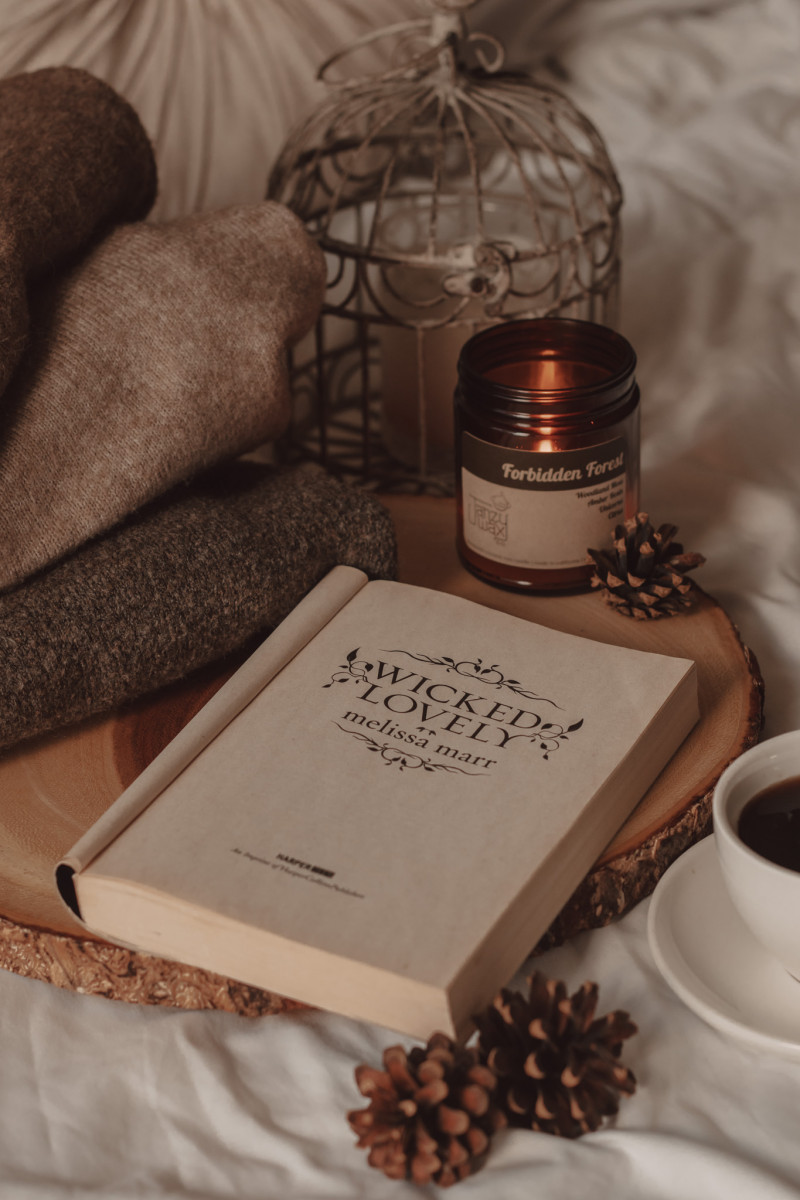 Wicked Lovely by Melissa Marr open to reveal the title page by a burning candle and a mug of black coffee