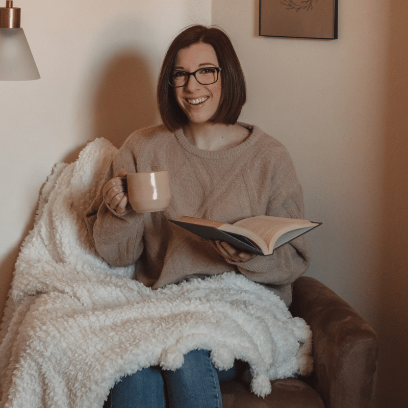 girl holds coffee mug while reading book