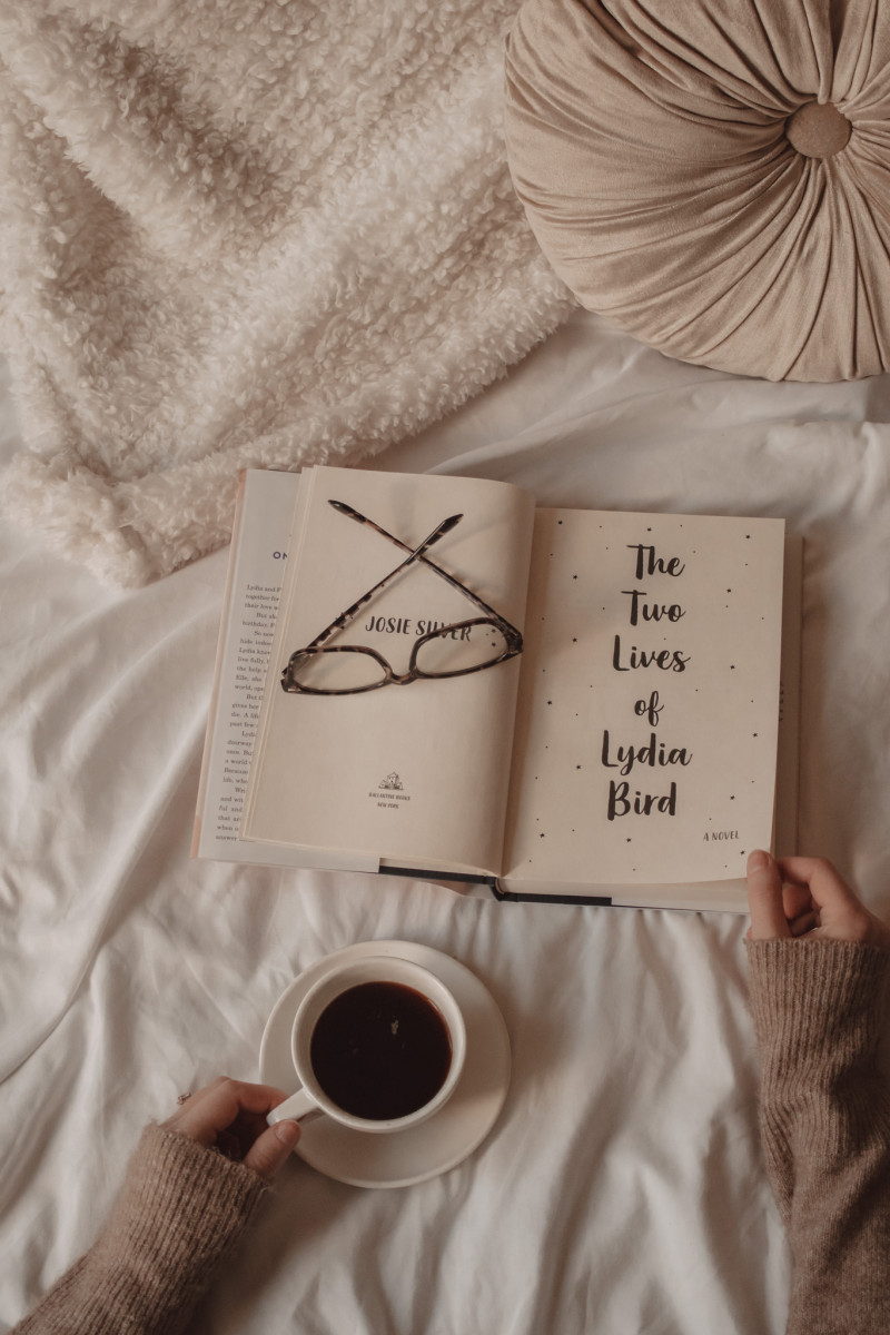 hands holding open the two lives of lydia bird with mug of black coffee and glasses