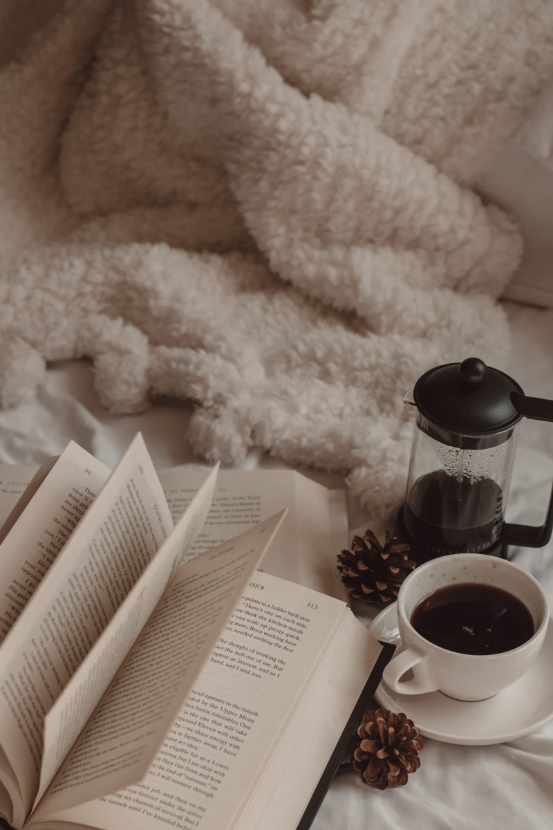 a book with flipping pages laying on a fluffy white blanket with small pinecones and a french press of black coffee and a mug nearby