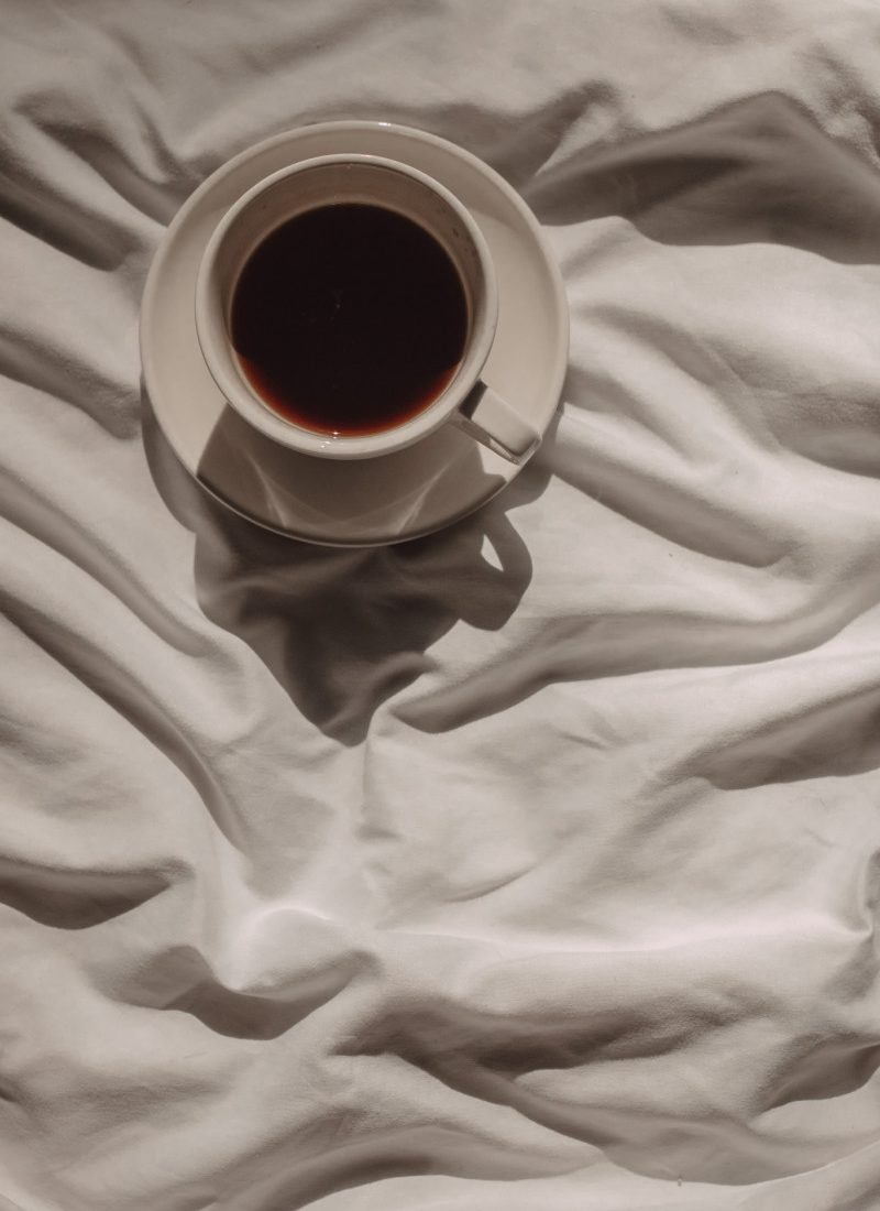a mug of black coffee in a saucer sitting on white sheets