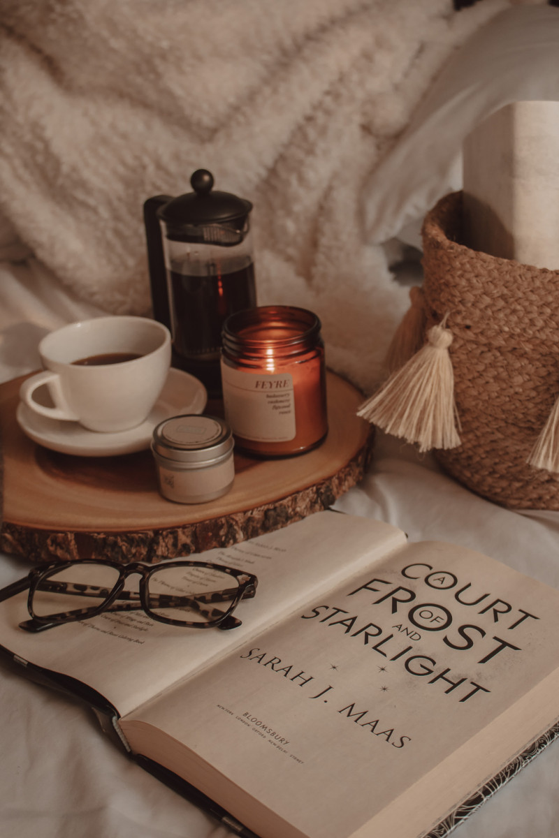 a court of frost and starlight book opened with glasses resting on top next to mug of coffee and burning candle