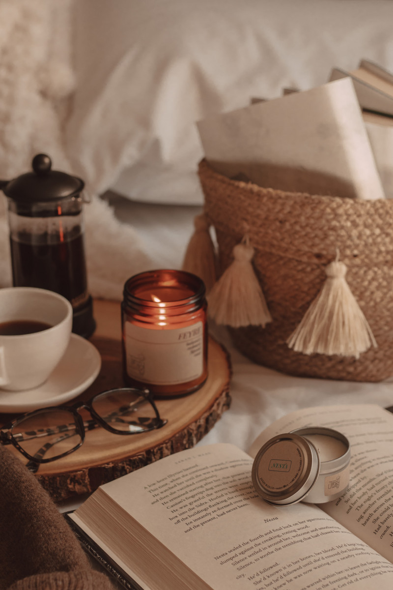 candle burning next to mug of coffee and glasses with a small candle on top of a book