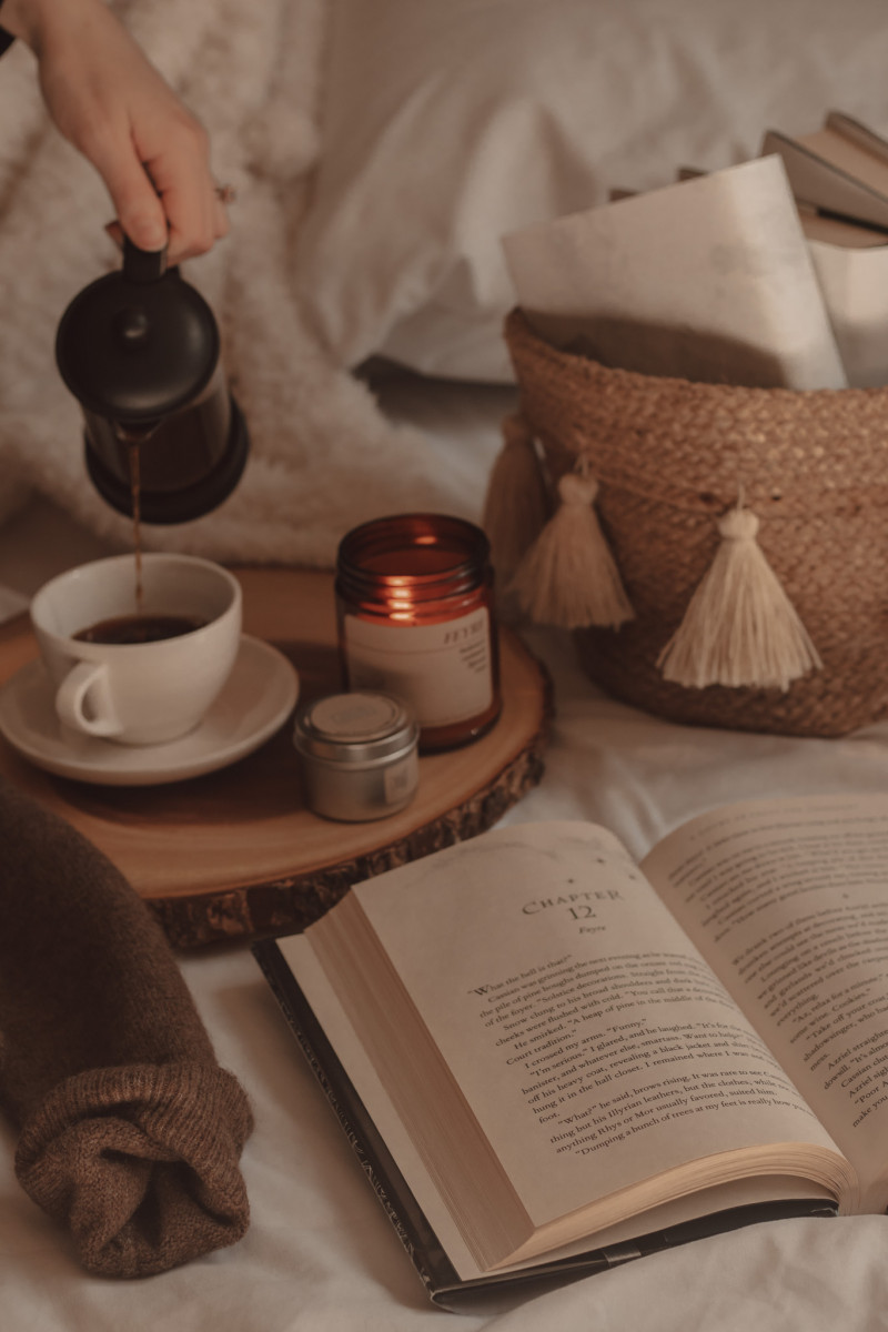 book opened next to a couple of candles and coffee being poured into a mug