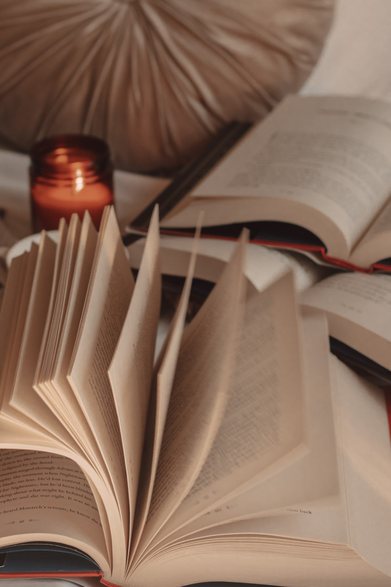 book pages flipping in the foreground with a burning candle and two stacked books in the background