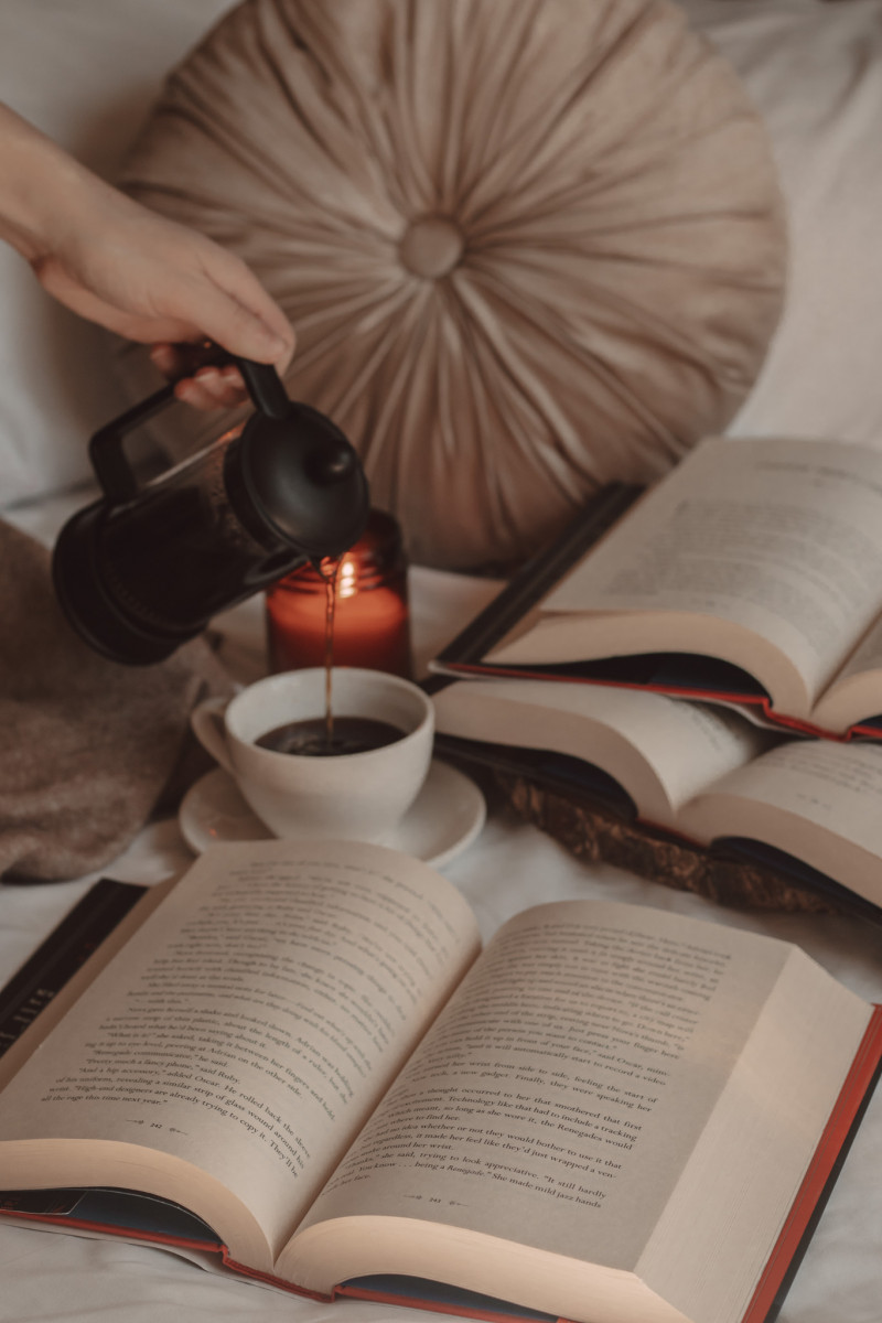 hand pouring coffee from a french press into a mug next to three open books and a lit candle