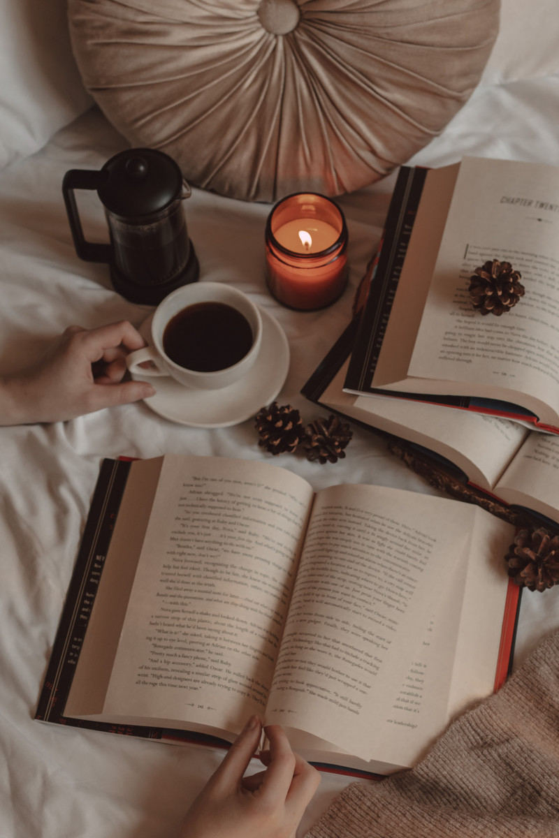 hand holding a mug of black coffee next to a french press and lit candle. beside it two books lay open on top of each other and a page is turned on a third book