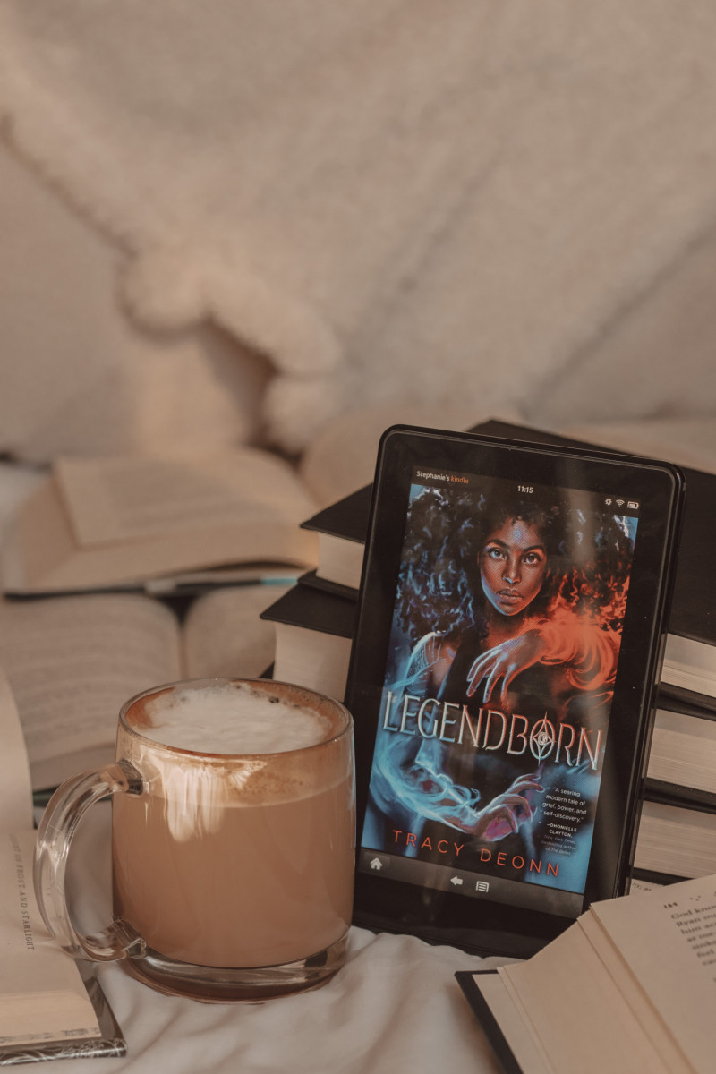 Legendborn book cover on a Kindle propped against a stack of black books next to a clear mug that holds coffee and foam