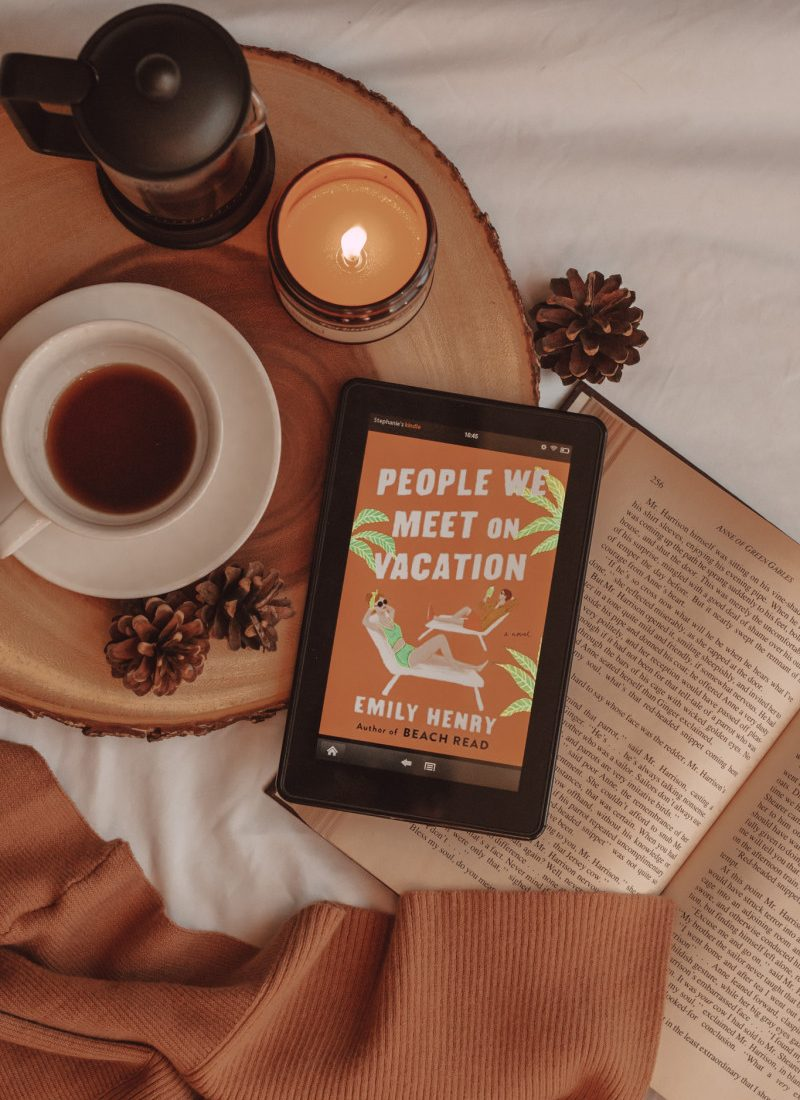 "from above, you can see an e-reader with the book cover for ""people we meet on vacation"" laying on an open book. next to it are a mug of coffee, a french press, and a lit candle."