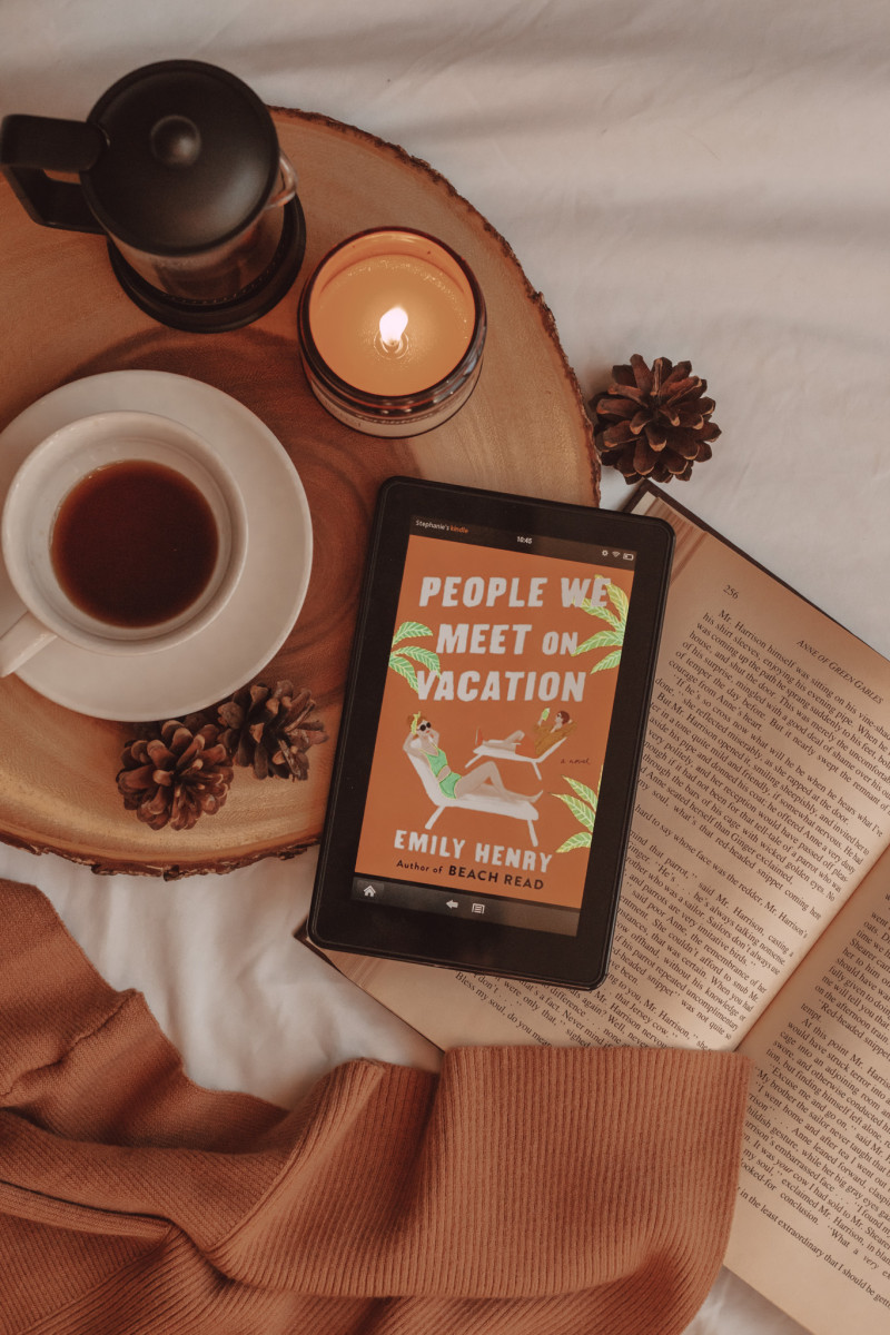 """from above, you can see an e-reader with the book cover for """"people we meet on vacation"""" laying on an open book. next to it are a mug of coffee, a french press, and a lit candle."""