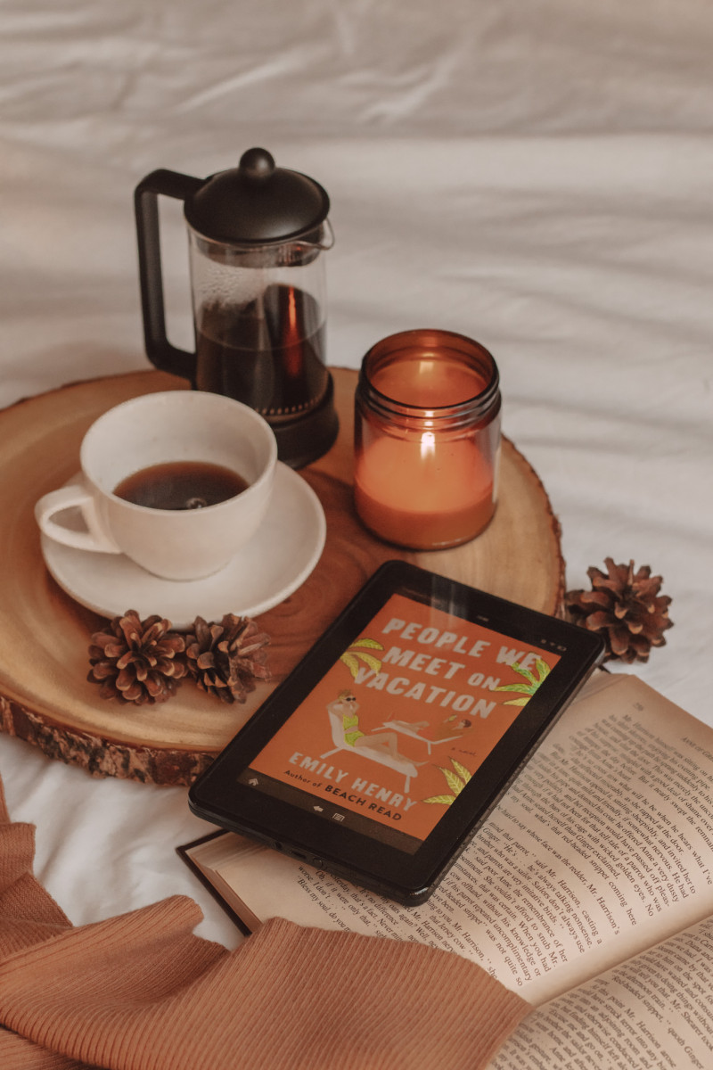 """a kindle sits on top of an open book with """"people we meet on vacation"""" shown on the screen. a lit candle, mug of coffee, and french press sit beside it."""