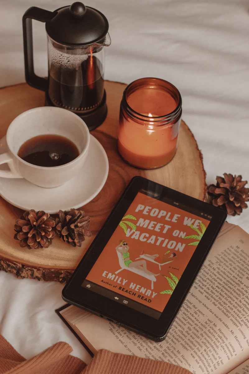 """kindle with the cover of """"people we meet on vacation"""" shown on the screen. a mug of coffee, a french press, and a lit candle sit beside it"""