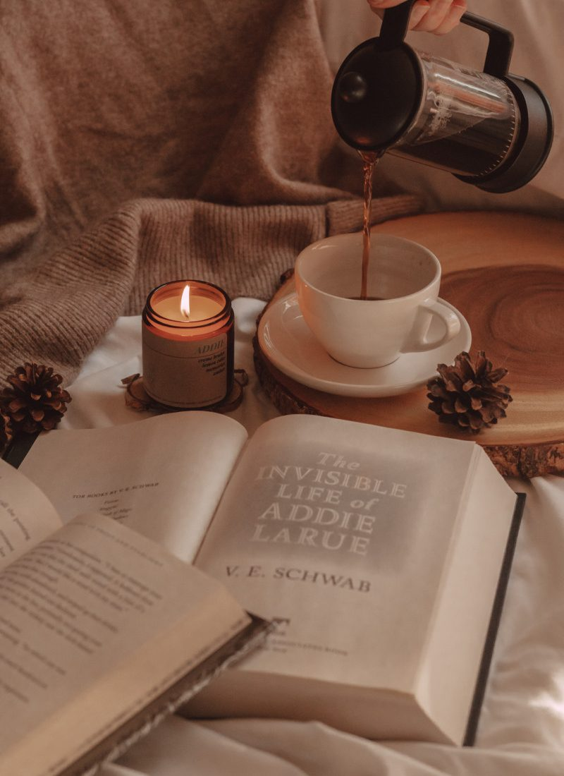 coffee being poured into a mug next to a lit candle with two open books int he foreground
