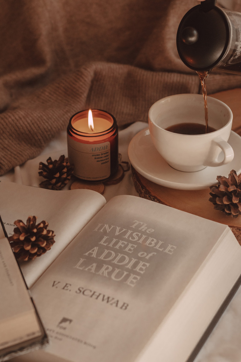 a close-up of the title page of the invisible life of addie larue with a lit candle and coffee being poured into a mug in the background